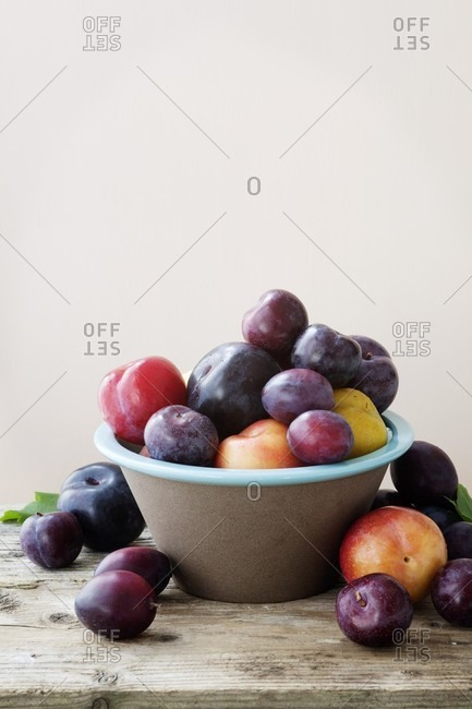 Plums in an earthenware bowl against a peach color background