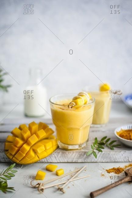 Mango lassi with turmeric and honey, fresh mango on a side