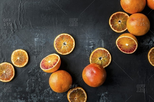 Blood oranges: whole, halved and sliced on a black background