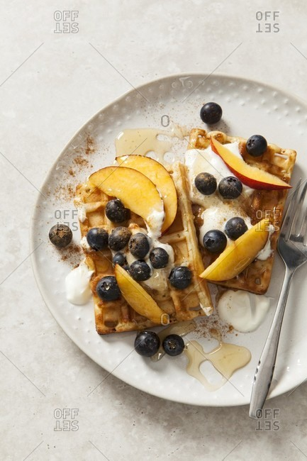 Belgian waffles with yoghurt, honey, blueberries and peach wedges