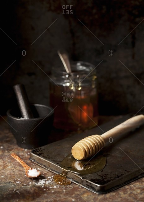 Honey on a wooden drizzler and sea salt