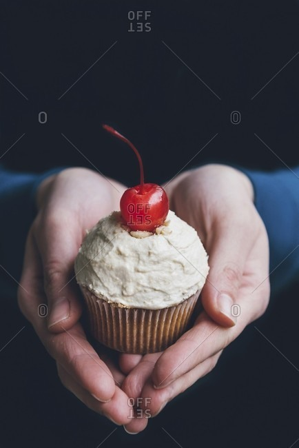 Hands holding a cupcake with peanut frosting and a cocktail cherry