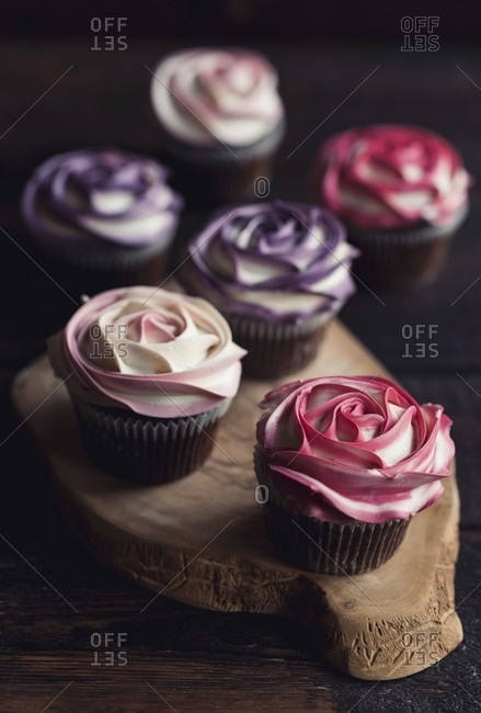 Sweet roses cupcakes on the wooden board