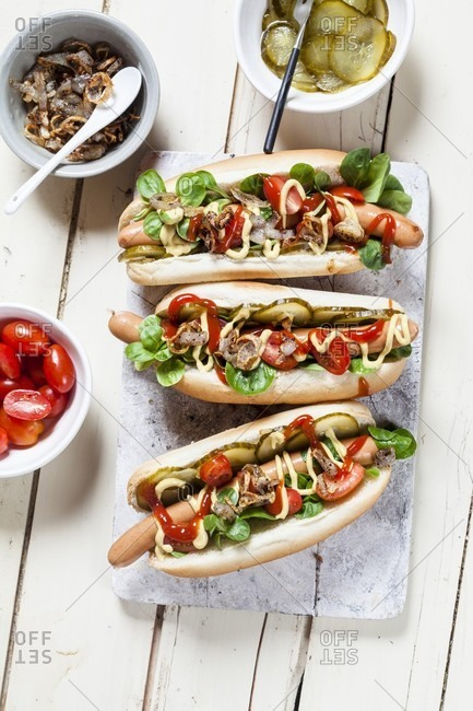 Hot dogs with lettuce, tomatoes, gherkins, ketchup, mustard and toasted onions