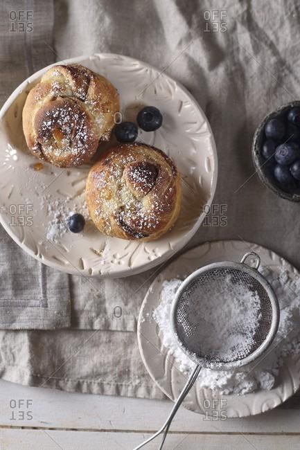 Orange brioche with chocolate, powdered sugar, and blueberries