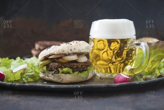 A bean burger in a sesame buns, with radishes and beer (vegan)