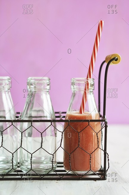 A bottle of watermelon smoothie with a straw in a wire basket
