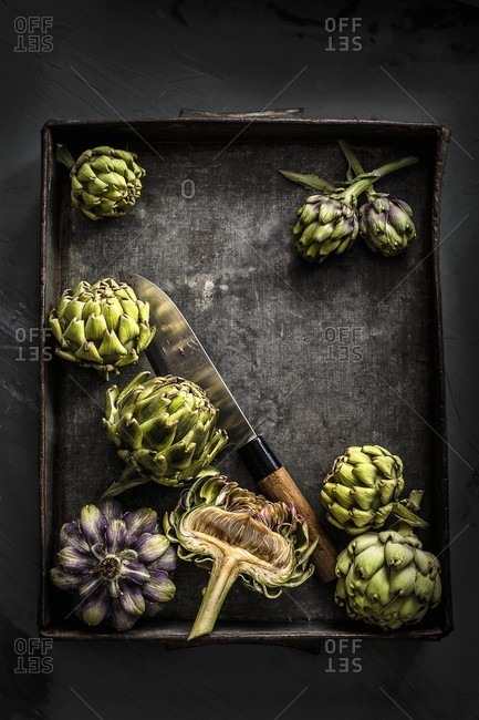 Whole and halved artichokes on a black metal tray