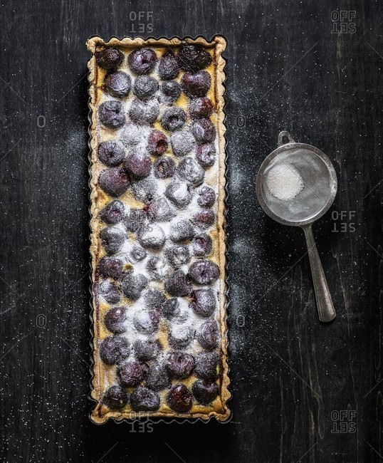 A rectangular cherry tart sprinkled with icing sugar