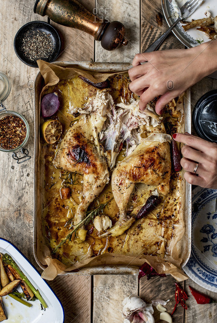 Partially eaten roasted chicken and female hands