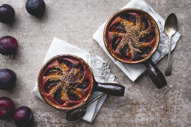 Dairy free plum clafoutis on a stone background and plums, autumn style.