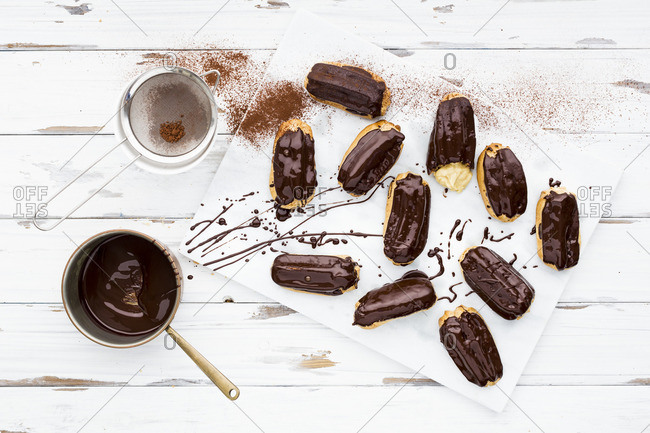 Spelt eclairs made with choux pastry topped with dark chocolate and stuffed with creme patisserie on a wood and marble background