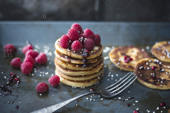 Vegan pancakes with chocolate sauce, raspberries and popped amaranth