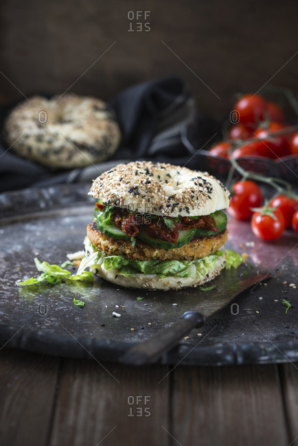 A chickpea and courgette fritter in a sesame seed bagel with dried tomatoes, lettuce and cucumber (vegan)