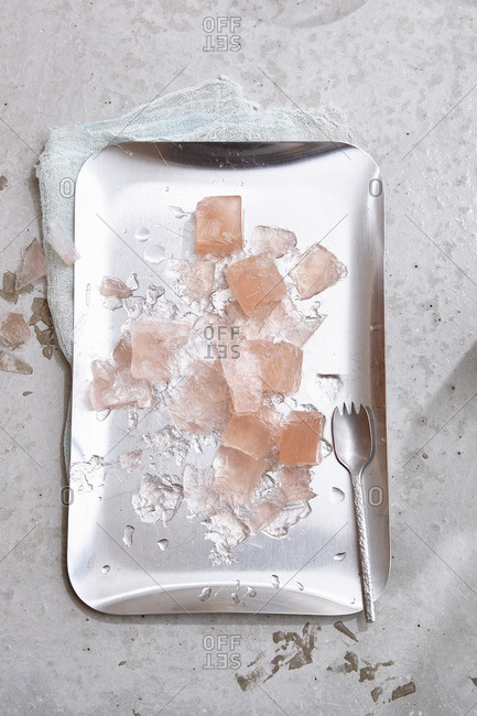 Rose wine ice cubes and ice splinters on a silver tray