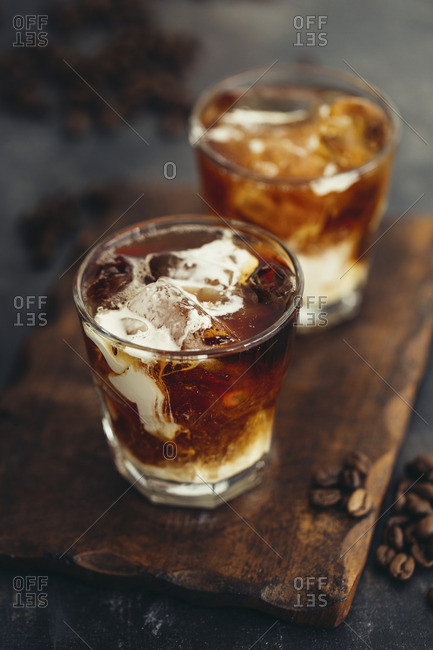 Two glasses of iced coffee with milk on a wooden board