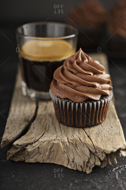Dark chocolate cupcakes with ganache frosting on dark background with espresso in a glass