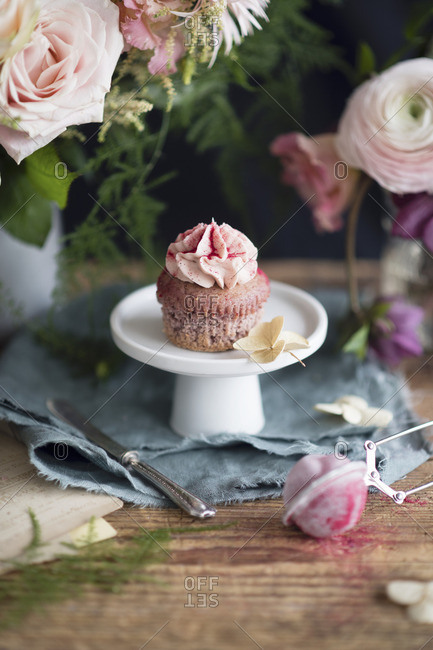 Strawberry milkshake cupcake with pink frosting on a mini cake stand surrounded by flowers