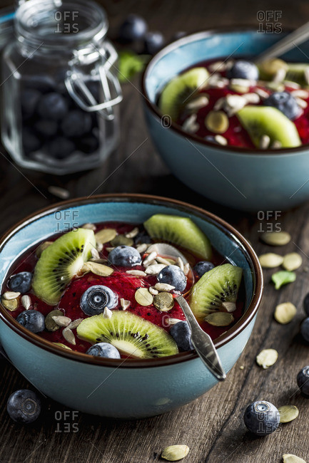 Strawberry-blueberry smoothie with fresh blueberries, kiwi, pumpkin and sunflower seeds