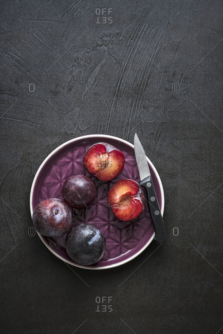 Whole and open red plums with knife on purple plate and dark background