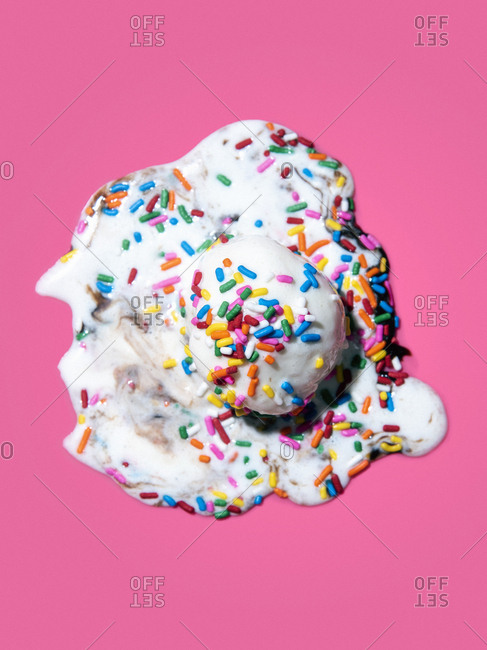 A scoop of ice cream melting in a puddle with chocolate sauce and rainbow sprinkles on a pink background