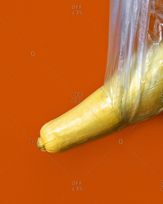 A yellow zucchini squash poking through a plastic bag