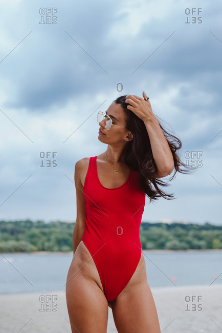 Attractive brunette woman in red one piece swimming suit posing on the beach