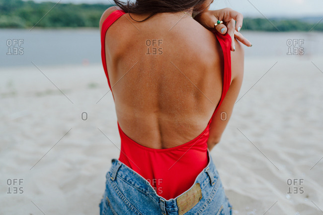 Woman in one piece red swimsuit and jeans shorts