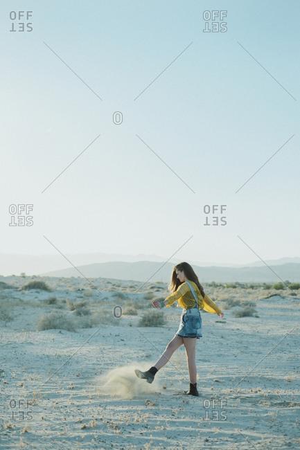 Girl kicking dust in the desert
