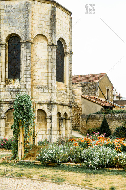 Yard in a french old town with back of a church and plenty of flowers