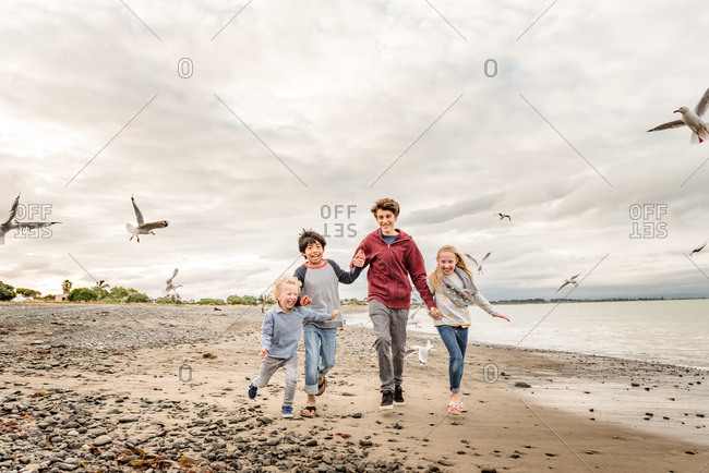 Happy children running on a beach together in New Zealand