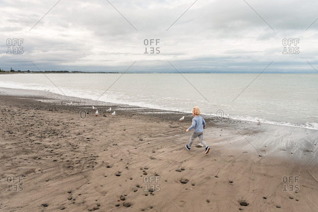 Young boy running on beach in New Zealand