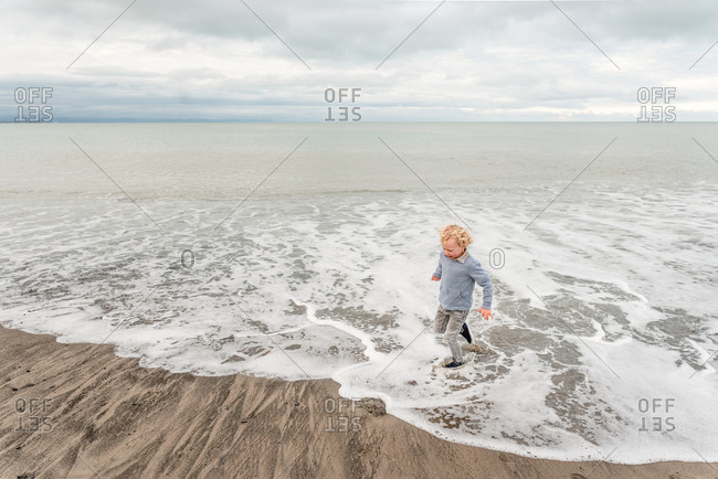 Young boy running in waves on beach in New Zealand