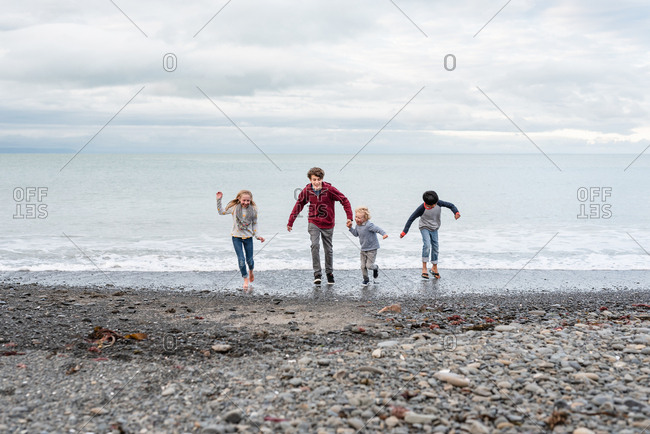 Children running in waves on coast of New Zealand