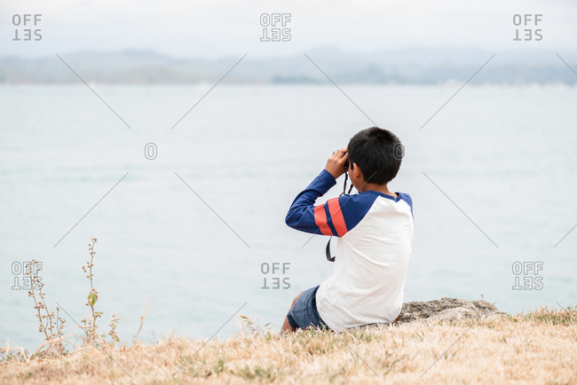 Boy with binoculars sitting on the coast of New Zealand
