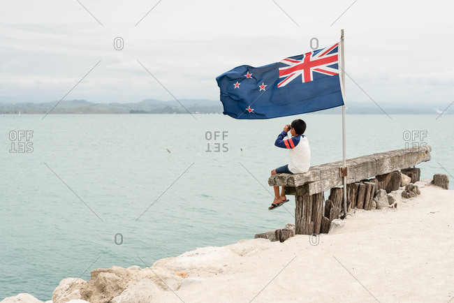 Boy sitting by flag with binoculars on the coast of New Zealand