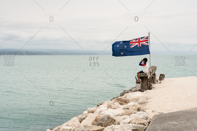 Young boy sitting by flag with binoculars on the coast of New Zealand