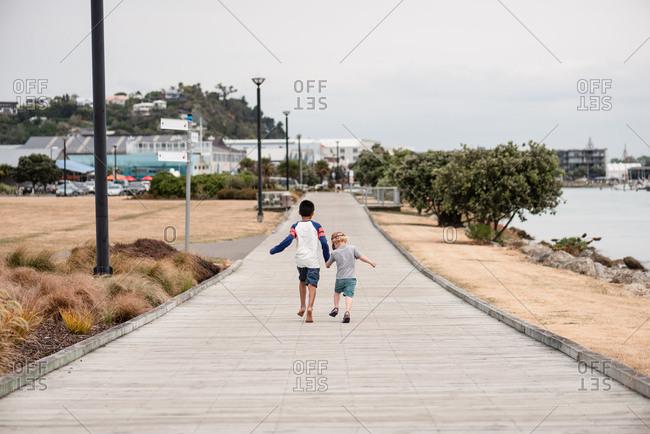 Two boys walking hand in hands beside the ocean in New Zealand