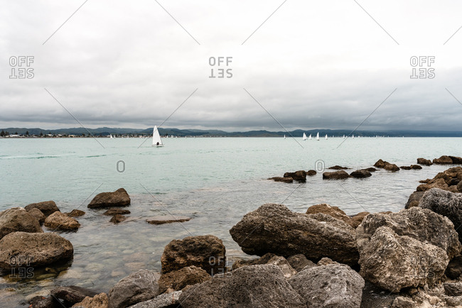 Sailboats in the ocean under stormy skies