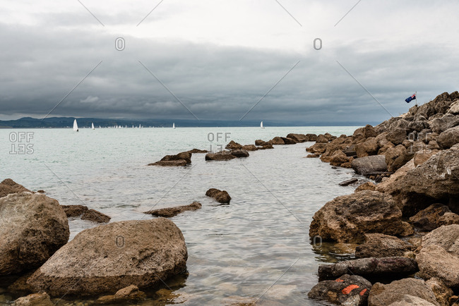 Sailboats off rocky coast in the ocean under stormy skies