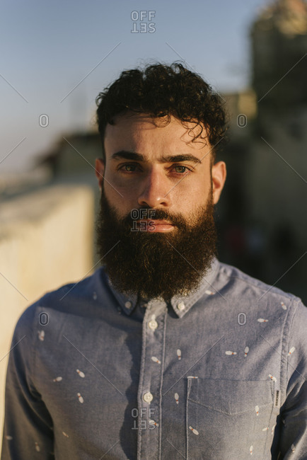 Portrait of a young handsome bearded man in a fun button up shirt