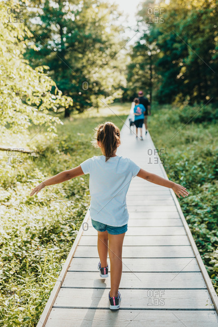 Girl with outstretched arms walking on boardwalk through natural area