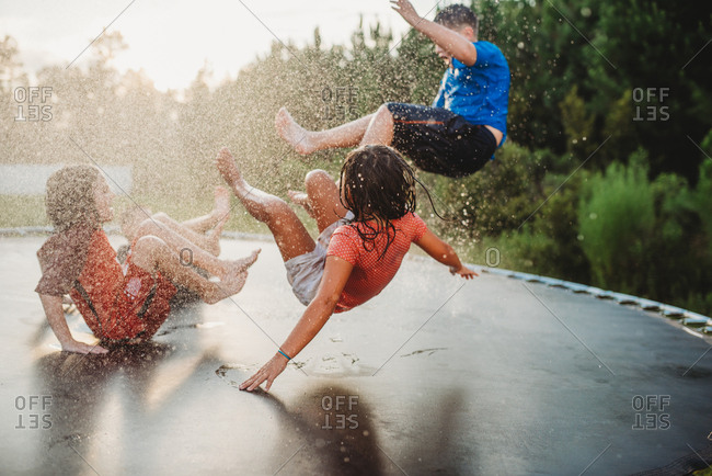 Children bouncing on trampoline while being sprayed with water