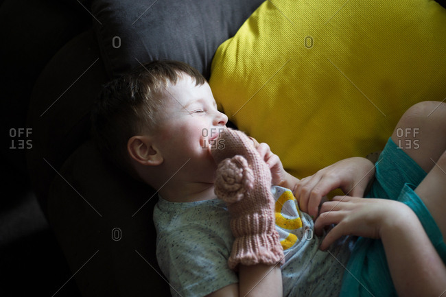 Laughing boy lying on couch being tickled