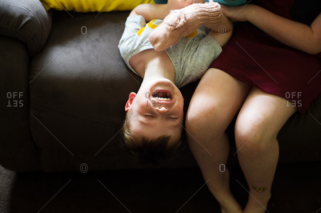 Laughing boy lying upside down being tickled