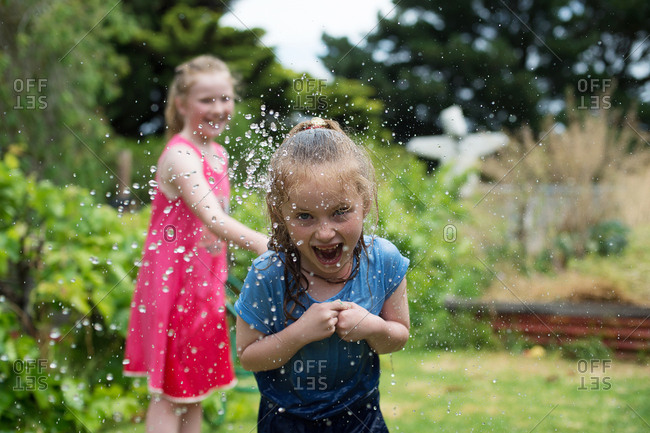 Laughing girl getting sprayed by garden hose