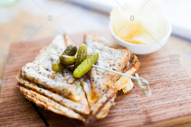 Grilled sandwich topped with small pickles on knotted pick