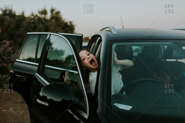 Girl making silly face while leaning out of car
