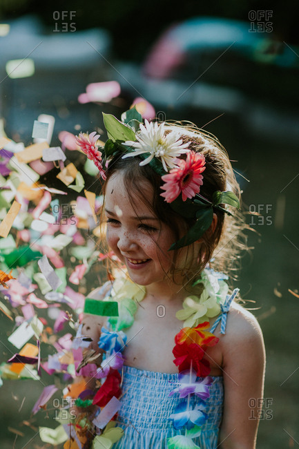 Young girl wearing lei surrounded in confetti