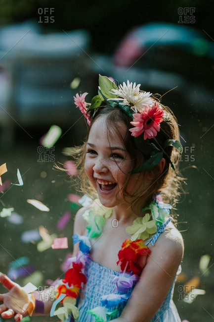 Little girl wearing lei surrounded in confetti